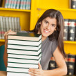 Student With Piled Books Sitting At Table In Library — Stock Photo