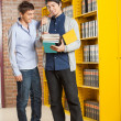 Male Students Looking At Book In College Library — Stock Photo