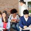 Students Writing Exam While Teacher Supervising Them In Classroo — Stock Photo #34906301