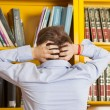 Student Pulling Hair Against Bookshelf In University Library — Stock Photo