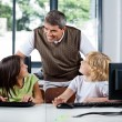 Teacher Assisting Schoolchildren In Using Desktop Pc — Stock Photo #34907711