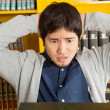 Student With Hands Behind Head Looking At Books In Library — Stock Photo