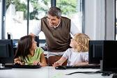 Teacher Assisting Schoolchildren In Using Desktop Pc — Stock Photo