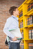 Student Holding Books While Looking At Shelf In Library — Stock Photo