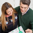 Smiling Couple Looking At Christmas Gift — Stock Photo
