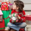 Stock Photo: Boy Holding Christmas Gift While Sitting On Floor