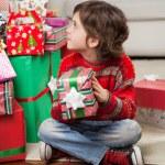 Boy Holding Christmas Gift While Sitting On Floor — Stock Photo