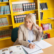 Teacher Writing In Book At University Library — Stock Photo #34928827