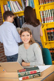 Student With Laptop While Friends Standing In Background At Libr — Stockfoto