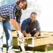 Workers Measuring Wood Together At Construction Site — Stock Photo #35182529