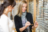 Woman Examining Eyeglasses With Salesgirl — Stock Photo