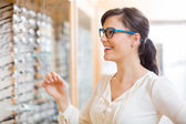Happy Woman Trying Glasses At Optician Store — Stock Photo