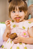 Girl Eating Birthday Cake With Icing On Her Face — Stock Photo