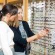 Happy Woman With Salesgirl Examining Eyeglasses — Stock Photo #35229099