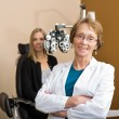 Stock Photo: Female Optometrist With Patient In Background