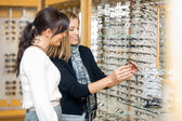 Happy Woman With Salesgirl Examining Eyeglasses — Stockfoto