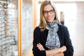 Woman Wearing Glasses With Arms Crossed In Store — Stock Photo