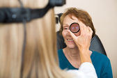 Optician Examining Senior Woman's Eye — Stock Photo