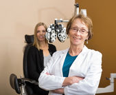 Female Optometrist With Patient In Background — ストック写真