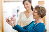 Senior Woman Holding New Glasses In Store — Stock Photo