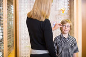 Mother Trying Spectacles On Son At Shop — Stock Photo