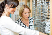 Salesgirl Assisting Woman In Selecting Glasses — Stock Photo