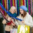 Mother And Daughter Selecting Tinsels At Store — Photo