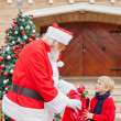 Boy Looking At Santa Claus While Taking Gift From Him — Stockfoto #35257969