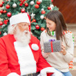 Girl Holding Gift While Looking At Santa Claus — Stock Photo