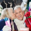 Senior Woman Kissing Man With Christmas Presents — Foto de Stock