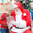 Boy And SantClaus Using Digital Tablet — Stock Photo #35259483