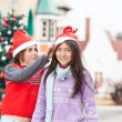 Girl Smiling While Friend Putting Santa Hat On Her Head — Stock Photo