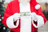 Babbo natale tenendo nota un dollaro — Foto Stock
