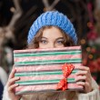 Woman Covering Face With Christmas Present At Store — Stok fotoğraf