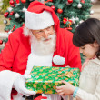 Santa Claus Giving Gift To Girl — Stock Photo #35261411