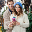 Couple With Gift Box Standing At Christmas Store — Стоковая фотография