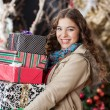 Woman Carrying Stacked Christmas Gifts In Store — Lizenzfreies Foto