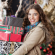 Woman Carrying Stacked Christmas Gifts In Store — Stok fotoğraf