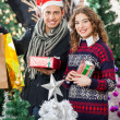 Couple Holding Christmas Presents At Store — Stock Photo #35265241