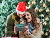 Pareja feliz celebración de presenta contra el árbol de navidad — Foto de Stock