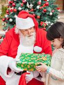 Papá noel dando regalos a chica — Foto de Stock