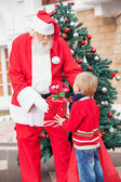 Santa Claus Giving Gift To Boy — Stockfoto
