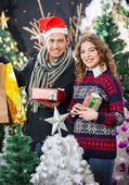Couple Holding Christmas Presents At Store — Stockfoto