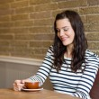 Attractive Woman Looking At Coffee Cup In Cafe — Stock Photo #35286059