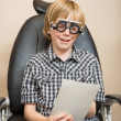 Постер, плакат: Boy With Trial Frame Reading Test Chart On Chair