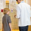 Stock Photo: Optometrist And Boy Choosing Eyewear In Store