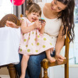 Girl Eating Cupcake While Sitting On Mother's Lap — Stock Photo #35288313