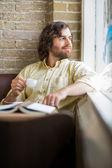 Muž s šálek kávy při pohledu přes okno v kavárně — Stock fotografie
