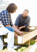 Worker Looking At Coworker Measuring Wood At Site — Stock Photo