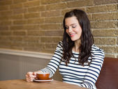Attractive Woman Looking At Coffee Cup In Cafe — Stock Photo
